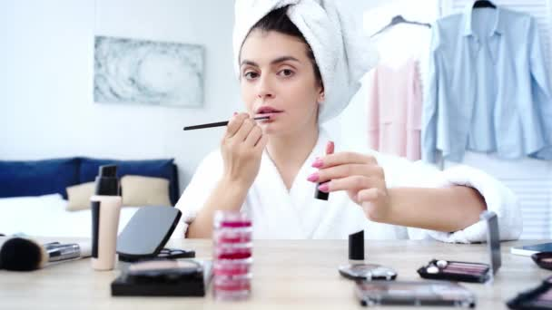 woman applying lipstick with cosmetic brush near table with decorative cosmetics