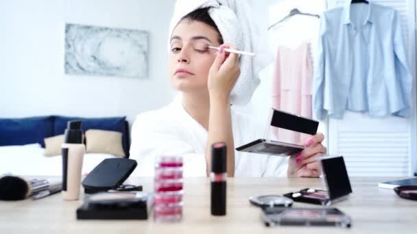 Žena, která používá oční stíny s kosmetickým kartáčem poblíž stolu s dekorativní kosmetikou