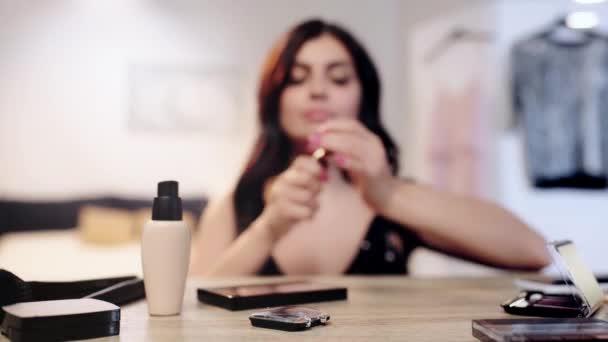selektivní zaměření ženy při odběru a aplikování rtěnky z tabulky s dekorativní kosmetikou