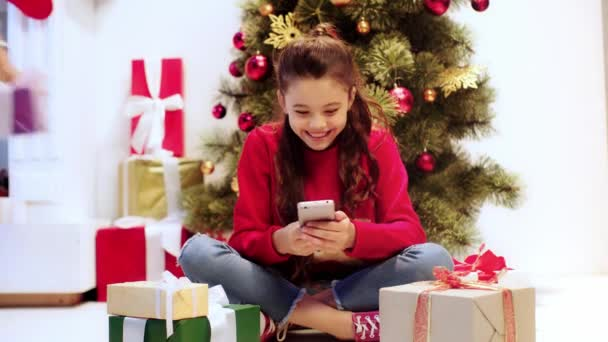 kid using smartphone near presents and parents