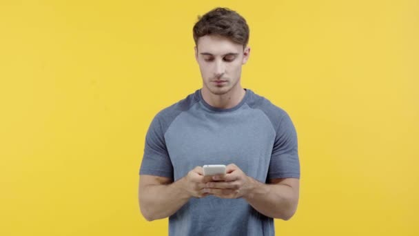 man texting on smartphone isolated on yellow