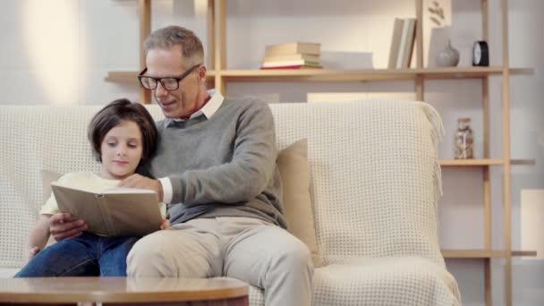 Opa und Enkel lesen gemeinsam Buch im Wohnzimmer