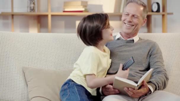 glücklicher Großvater und Enkel, die sich im Wohnzimmer umarmen und gemeinsam fernsehen