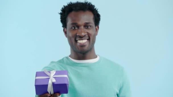 usmívající se africký Američan drží dárkové krabice izolované na modré