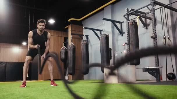 vousatý muž cvičit s závěsné řemínky v tělocvičně