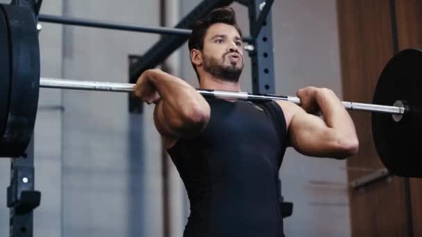 pohledný sportovec vzpírání činka v posilovně