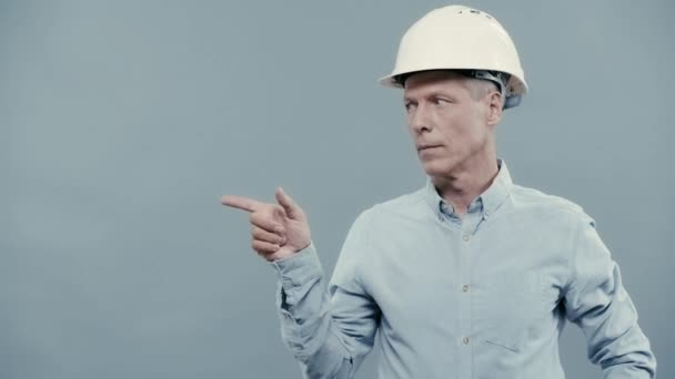 architect in helmet pointing with finger at copy space