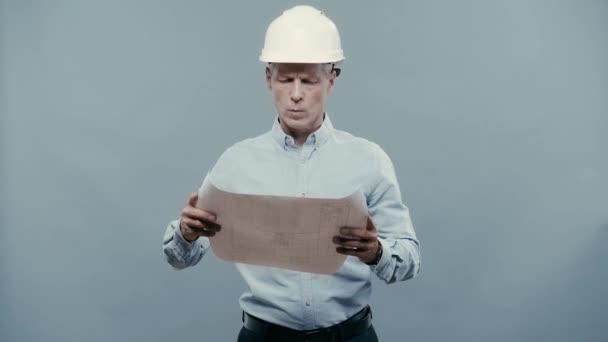 Architekt im Helm betrachtet Bauplan