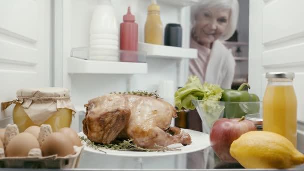 usmívající se žena s talířem s krocanem z lednice