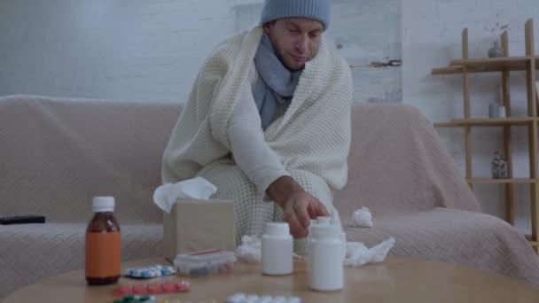 Kranker Mann sitzt mit Medikamenten am Tisch und nimmt Tabletten