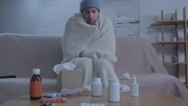 Erkrankter Mann niest, während er mit Medikamenten am Tisch sitzt