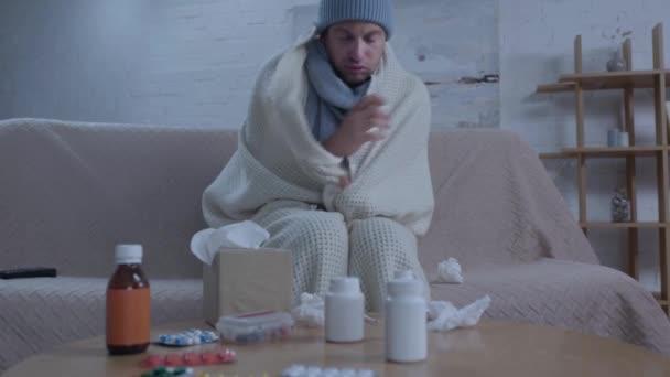 Kranker Mann sitzt mit Medikamenten am Tisch und benutzt Nasenspray