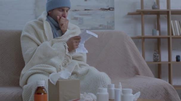 Kranker Mann sitzt mit Medikamenten und Leseanleitung am Tisch