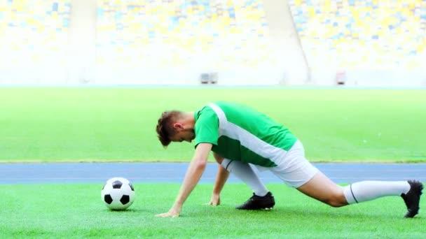 Seitenansicht des Fußballers, der die Beine streckt
