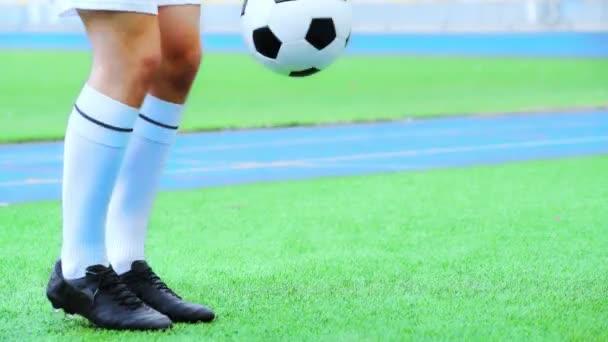 oříznutý pohled na fotbalistu skákající míč