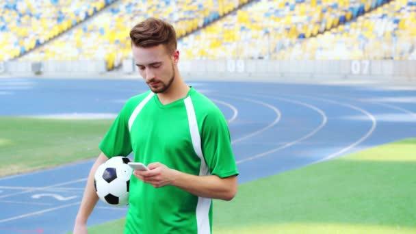 fotbalista drží míč a pomocí smartphonu
