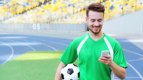 mosolygó labdarúgó holding ball és okostelefon használata