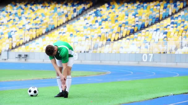 fotbalista protahuje nohy na stadionu