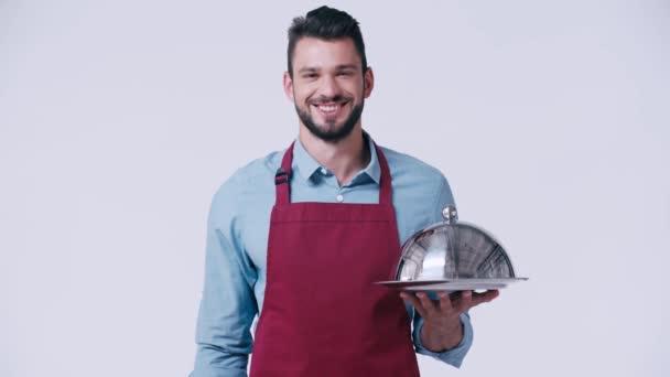 Lächelnder Kellner in Schürze mit Teller und Cloche isoliert auf weiß