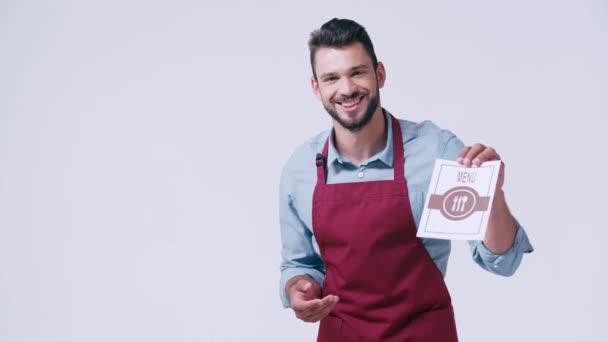 Lächelnder Kellner in Schürze zeigt Speisekarte isoliert auf Weiß
