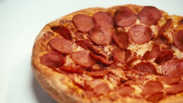 Selektivní zaměření lahodné pizzy točení na bílém pozadí