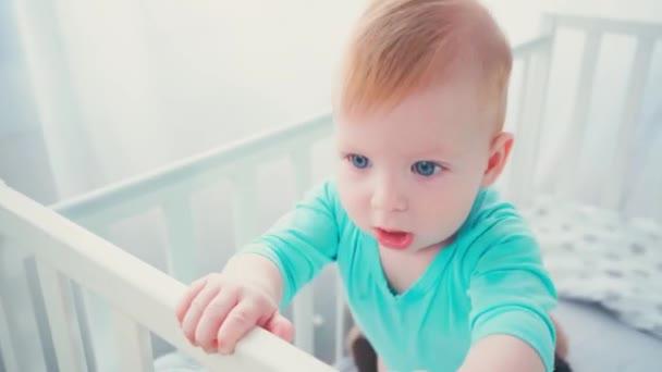 kojenec stojící v postýlce a dívající se na kameru