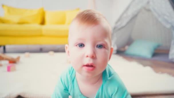 kisfiú nézi a kamerát, miközben mászik otthon