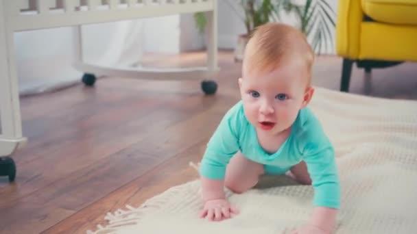 kojenec dívá na kameru, zatímco plazí doma
