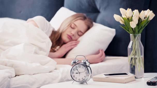 Selektivní zaměření spící ženy vypnutí budíku