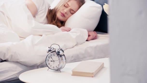 Alvó nő kikapcsolja az ébresztőórát