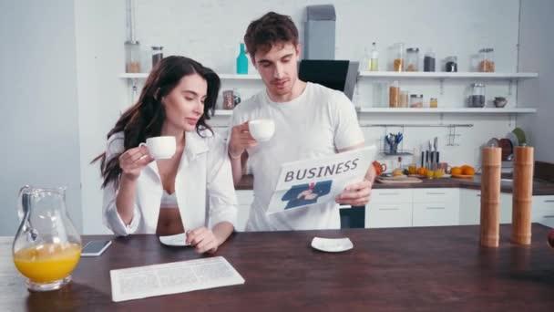 Mann hält Tasse und Zeitung neben Freundin in Bar und Hemd in Küche