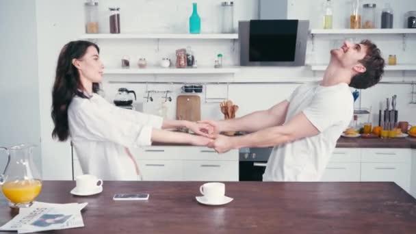 Sexy Paar tanzt neben Kaffee und Zeitungen auf Küchentisch