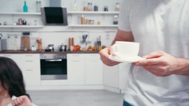 Mann gibt Kaffee an sexy Frau auf Sofa zu Hause