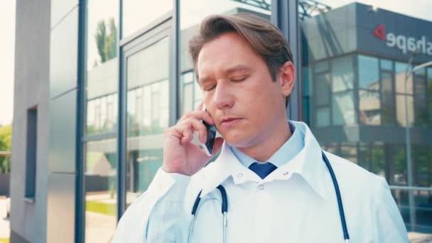 seriózní lékař mluví na smartphone v blízkosti budovy venku