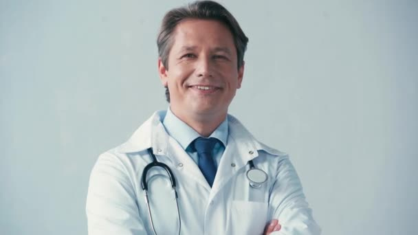 doctor in white coat with stethoscope looking at camera on grey