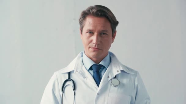 doctor in white coat holding cigarette and showing no gesture on grey