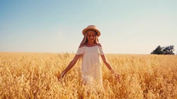 Mädchen in weißem Kleid und Strohhut spazieren im Weizenfeld