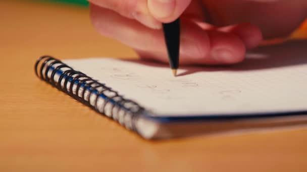 Stojan zaměření člověka psaní perem na spirálovém notebooku