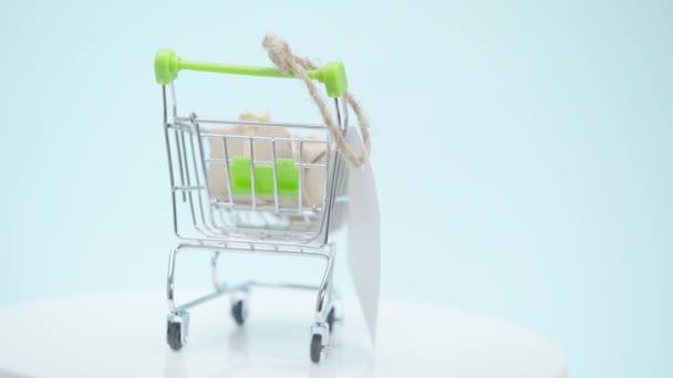 Selektivní zaměření nákupního košíku s dárky spinning na modrém pozadí