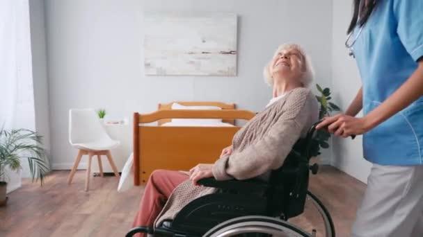 Krankenschwester bringt lächelnde ältere Frau im Rollstuhl ans Fenster
