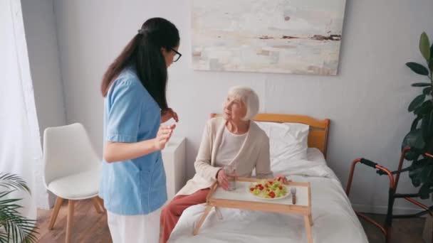 brunetka zdravotní sestra gestikulace při rozhovoru se starší ženou během snídaně