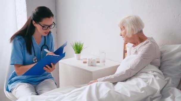 mladý geriatrician mluvení s věkem žena a psaní ve schránce