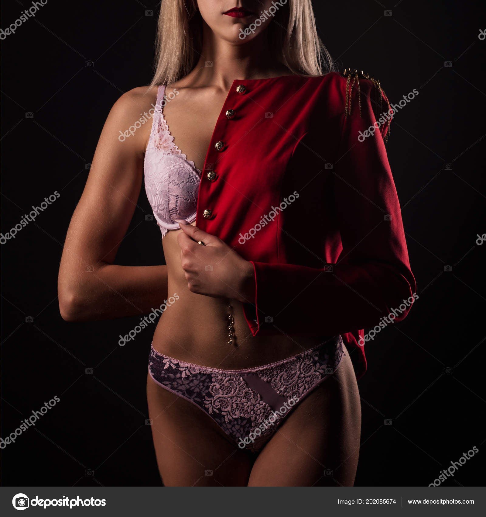 4915e16d05f Blonde young woman in lace lingerie and red jacket on dark background– stock  image