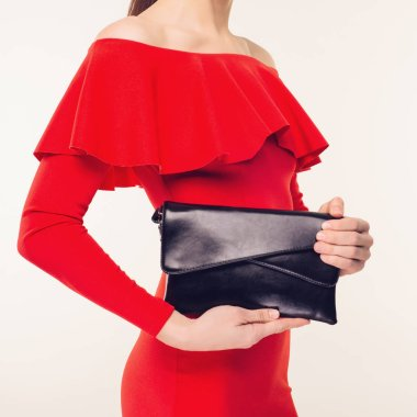 Fashionable woman with a black clutch in her hands and red evening dress on white background