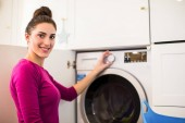 A fiatal, mosolygós nő ül a szobában mosógép, és bekapcsolja a mosógép