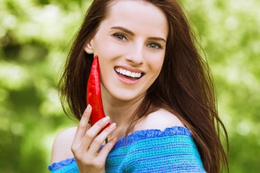 Portrait of young wonderful smiling woman with bare shoulders who keeps red pepper in hand near her face outdoor