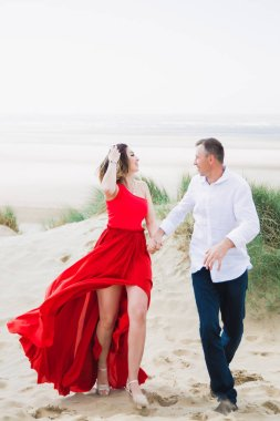 Happy romantic smiling couple stands in embrace against the background of sea