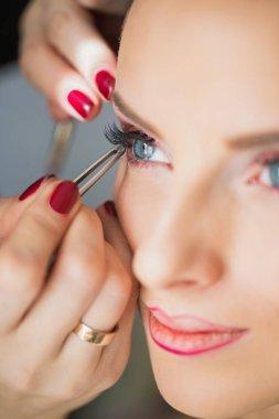Makeup artist applying false eyelash on eye of girl