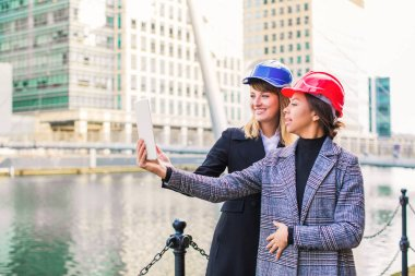 Happy young architects do selfie-photo on the tablet outdoors