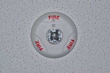A circular gray fire alarm attached to a white ceiling as seen from directly above, looking up.